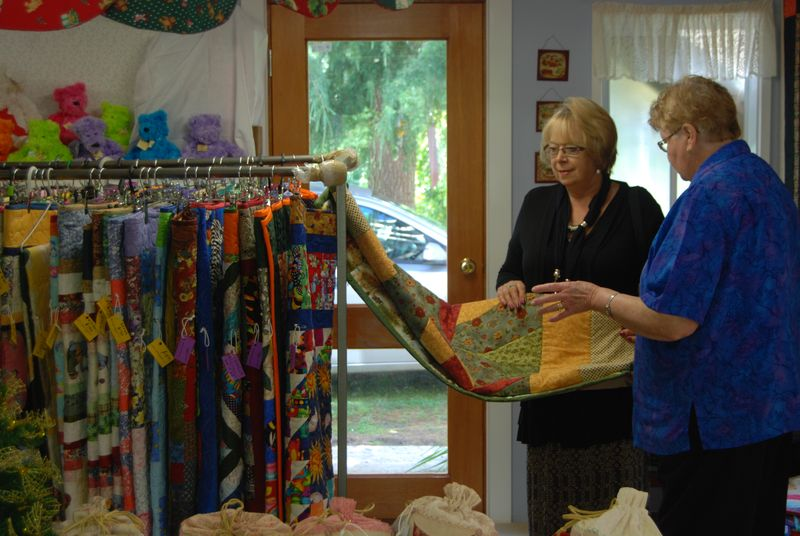 Quiltfair showing a buyer a quilt for sale